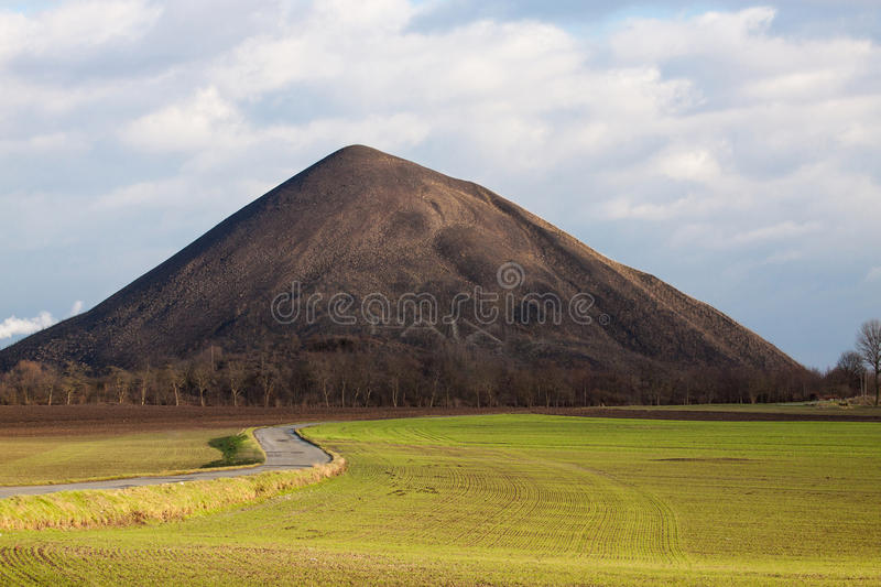 Coal tip. View of a coal tip with great light with fields and a road in front. It is written Paix that means peace in france on the tip stock photos