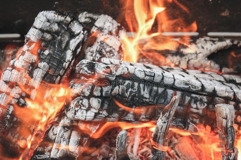 Coal from wood in a campfire with smoke and flame. Natural fire stock photo