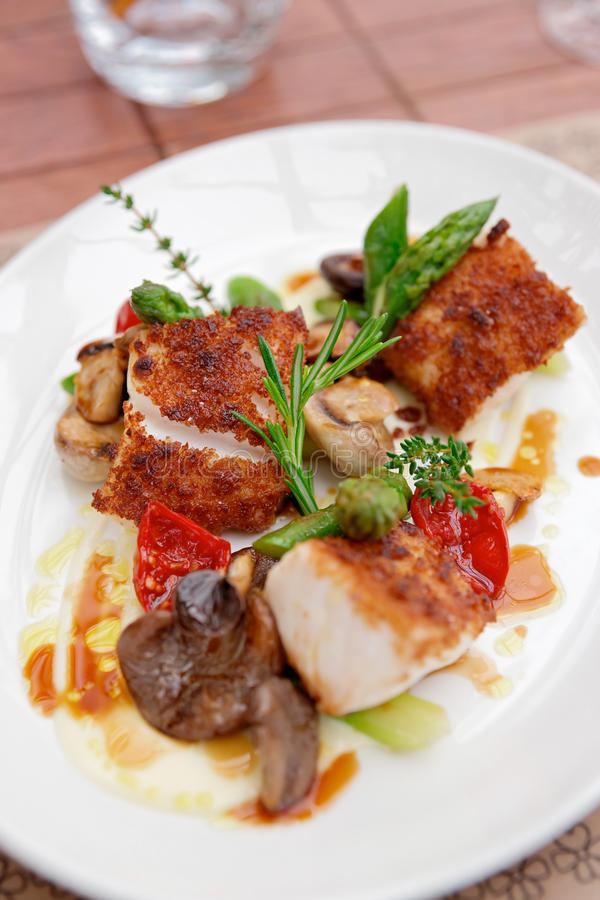 Coalfish fillet with mushrooms and asparagus. On plate stock photos