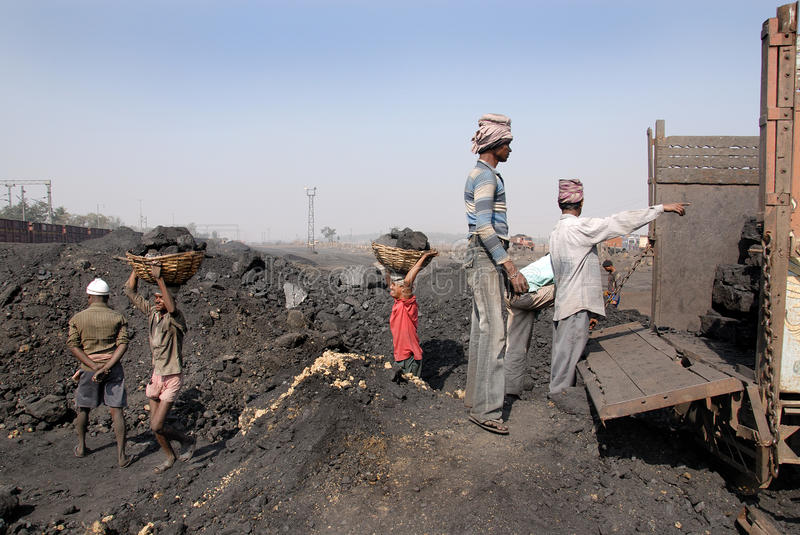 Coalmines in India. October 12,2011 Jharia,Jharkhand,India,Asia-A group of coal mines worker loading coal at the track in Jhariya coalfield area stock image