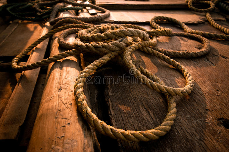 Coarse coconut rope at wooden fishing boat deck stock photography