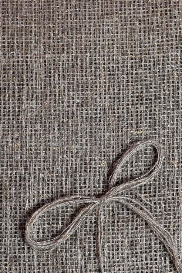 Coarse linen fabric. On it lies a bow of linen thread.  royalty free stock photos