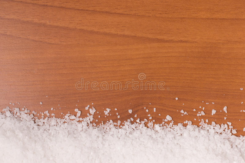 Coarse salt frame. Over a wooden table stock images