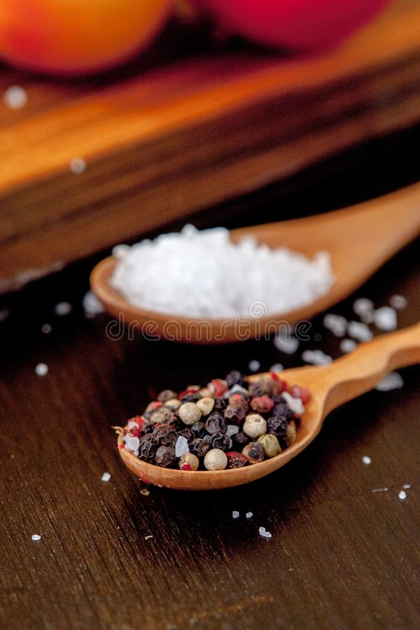 Coarse salt and pepper in a wooden spoon. royalty free stock images