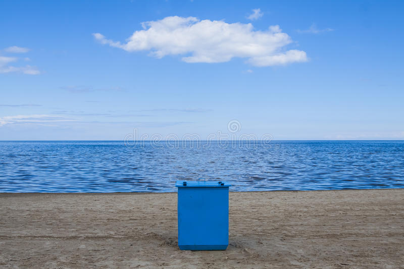 Coast, beach with calm seas. Symmetrical composition, in the center of the photo, the container in blue royalty free stock photo