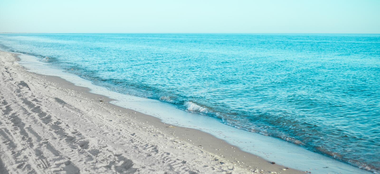 Coast of the blue sea with rolling waves. And white sandy beach stock photo
