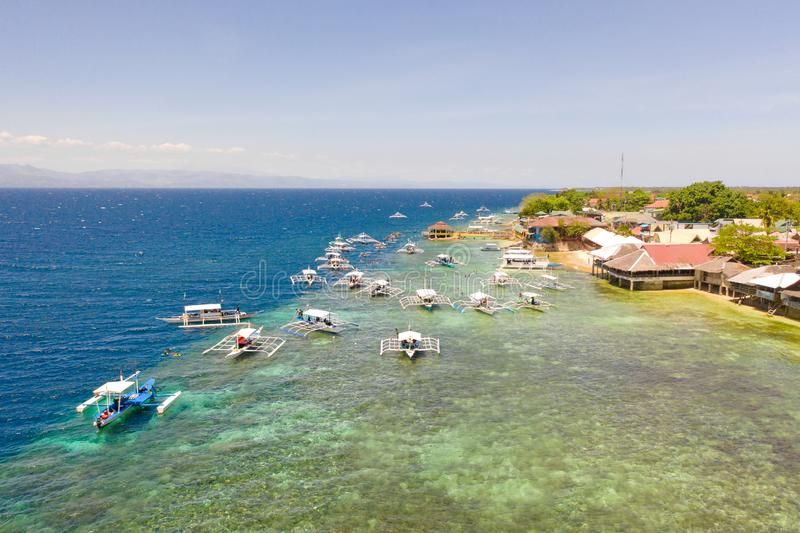 Coast of Cebu island, Moalboal, Philippines, top view. Boats near the shore in sunny weather. Seascape with coral reef near the shore royalty free stock image