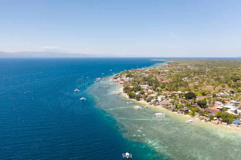 Coast of Cebu island, Moalboal, Philippines, top view. Philippine boats in a blue lagoon over coral reefs. Moalboal is a great place for diving and vacations stock images