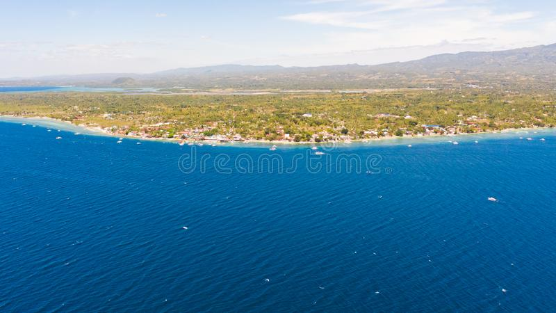 Coast of Cebu island, Moalboal, Philippines, top view. Philippine boats in a blue lagoon over coral reefs. Moalboal is a great place for diving and vacations royalty free stock photo