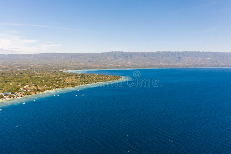 Coast of Cebu island, Moalboal, Philippines, top view. Philippine boats in a blue lagoon over coral reefs. Moalboal is a great place for diving and vacations stock image