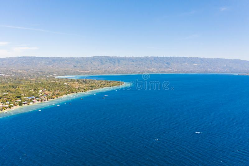 Coast of Cebu island, Moalboal, Philippines, top view. Philippine boats in a blue lagoon over coral reefs. Moalboal is a great place for diving and vacations stock photography