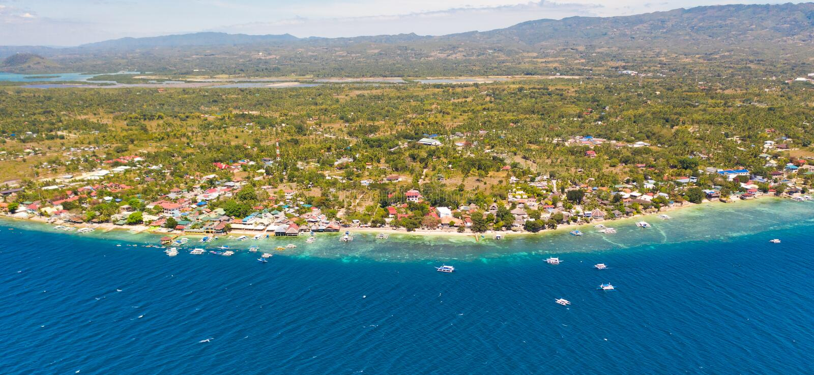 Coast of Cebu island, Moalboal, Philippines, top view. Philippine boats in a blue lagoon over coral reefs. Moalboal is a great place for diving and vacations stock photos