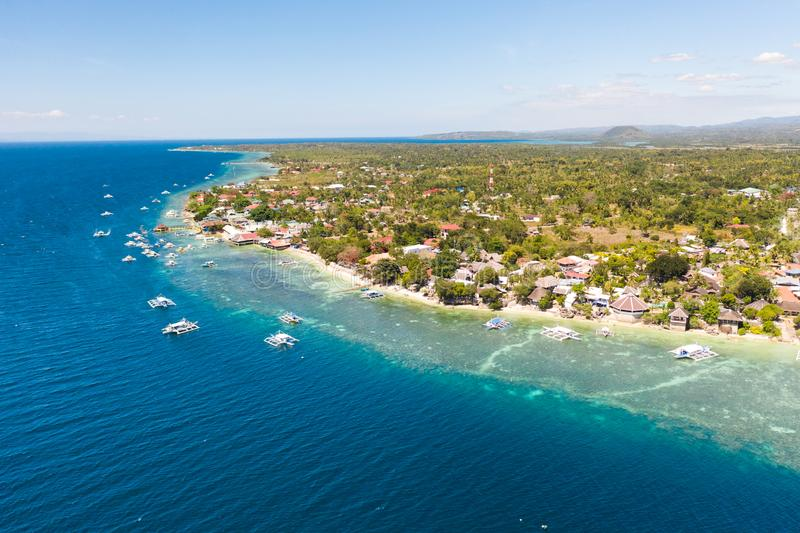 Coast of Cebu island, Moalboal, Philippines, top view. Philippine boats in a blue lagoon over coral reefs. Moalboal is a great place for diving and vacations stock photo