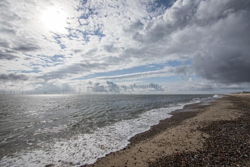 The coast of East Anglia Norfolk UK. Coastal view. With cloudy sky, pebbled beach and distant offshore wind farm turbines. Changeable weather from the sea stock photo