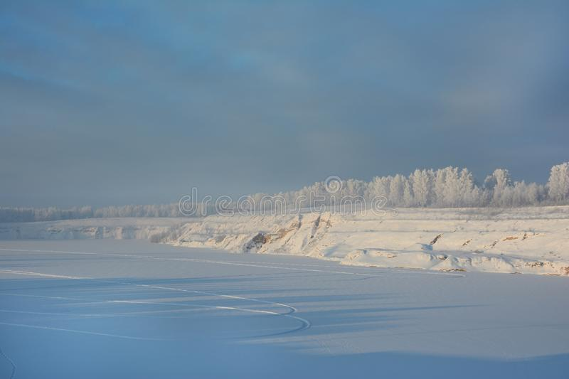 Coast of the frozen lake and the forest in the frosty winter afternoon stock image