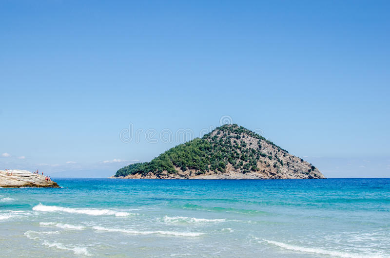Coast of The Greek island Thassos. Blue aegean sea. Coast of The Greek island Thassos. Blue aegean sea and a small rocky island nearby seen from paradise beach royalty free stock photo