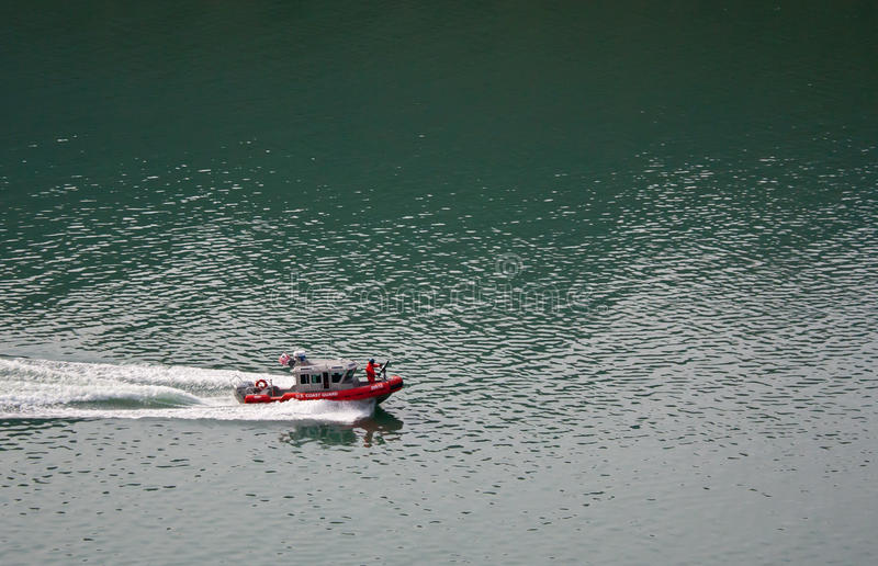 Coast Guard Ship Escort. An armed U.S. Coast Guard boat on the water escorting another ship royalty free stock photos