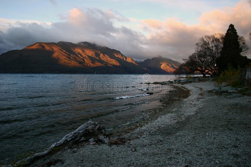 Scenic orange lit mountains and pebble beach on water at sunrise stock images