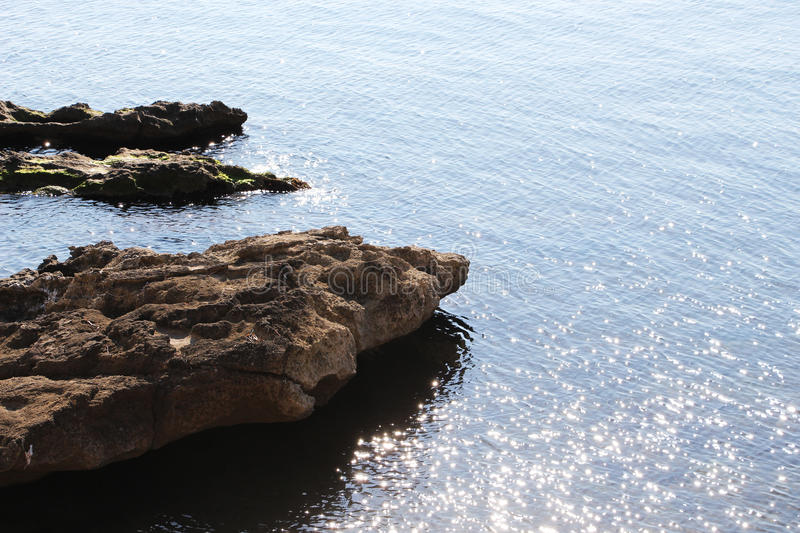 Coast line, with rocks and water reflections. A dazzling view of a coast line with some rocks and some circles of water reflections, taken in a very sunny day stock images