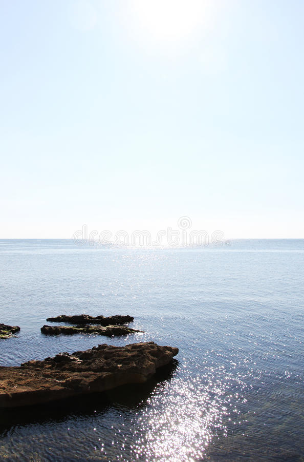 Coast line, with rocks and water reflections. A dazzling view of a coast line with some rocks and some circles of water reflections, taken in a very sunny day stock photo