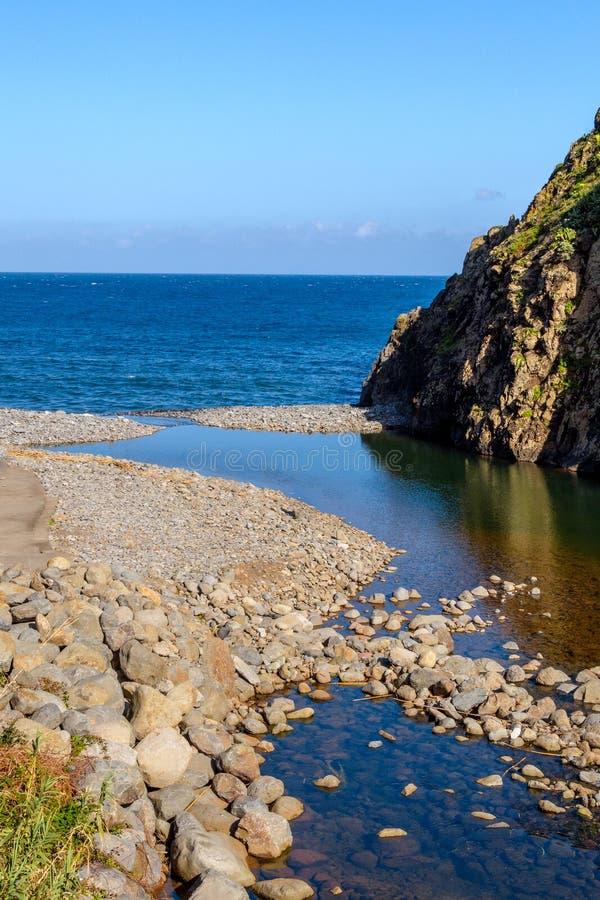 Coast near Sao Jorge, Madeira Island, Portugal. The mountain river flows into the ocean royalty free stock photography