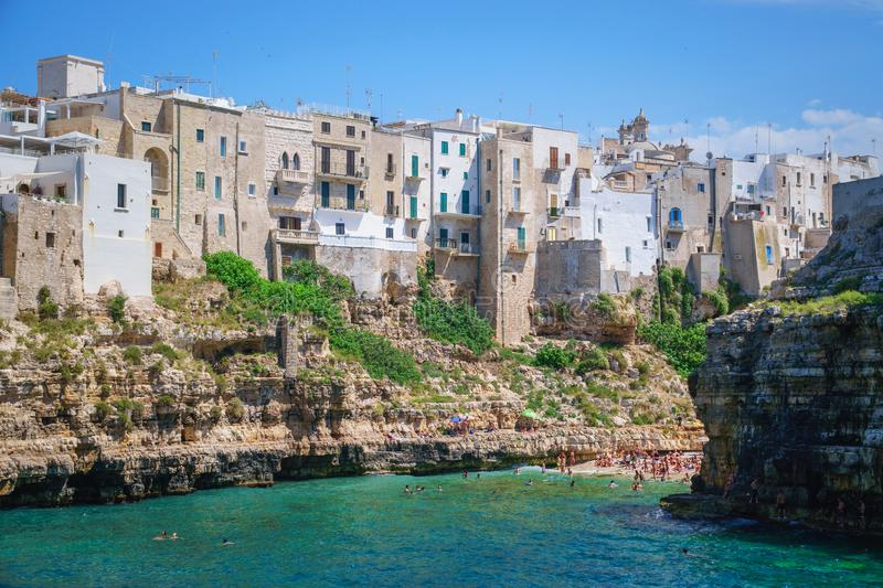 Coast of Polignano a Mare and beach with tourists, Puglia, Italy. View of sea from Polignano a Mare and beach with tourists, Puglia, Italy royalty free stock photo