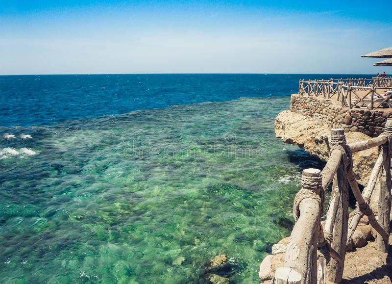 Coast of the Red Sea with a wooden fence and sun umbrellas in Sharm El Sheikh, Egypt royalty free stock image