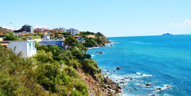 Coast, roofs, rocks, panoramic view on Salivoli, in Livorno, Tuscany, Italy. We can see rocks, trees, hills, horizon, clouds and blue sky, Tyrrhenian sea, in stock image