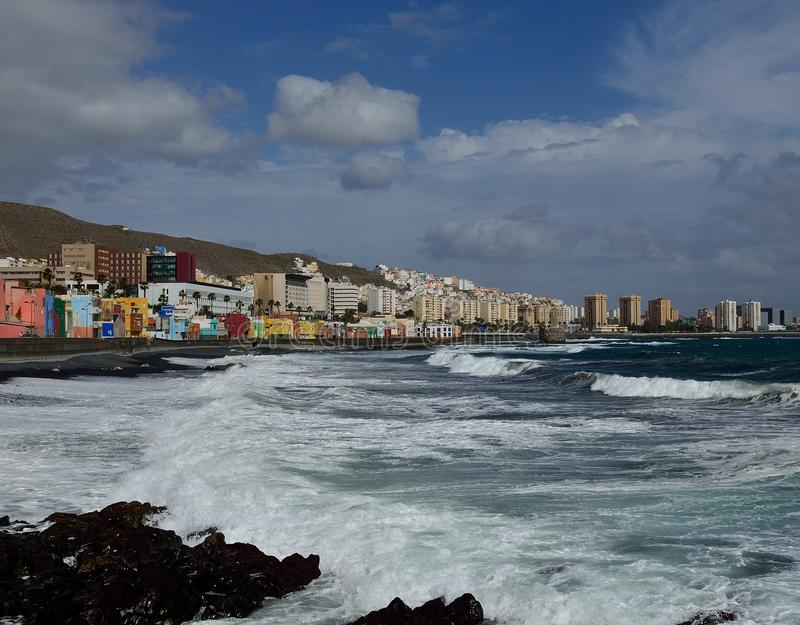 Coast with strong waves, Gran Canaria. Coast with strong waves, city in the background and cloudy sky, Las Palmas de Gran Canaria royalty free stock images