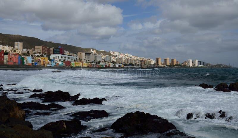 Coast with strong waves, Las palmas. Rocky coast with strong waves and Las Palmas city in the background, Gran Canaria, Canary Islands royalty free stock image