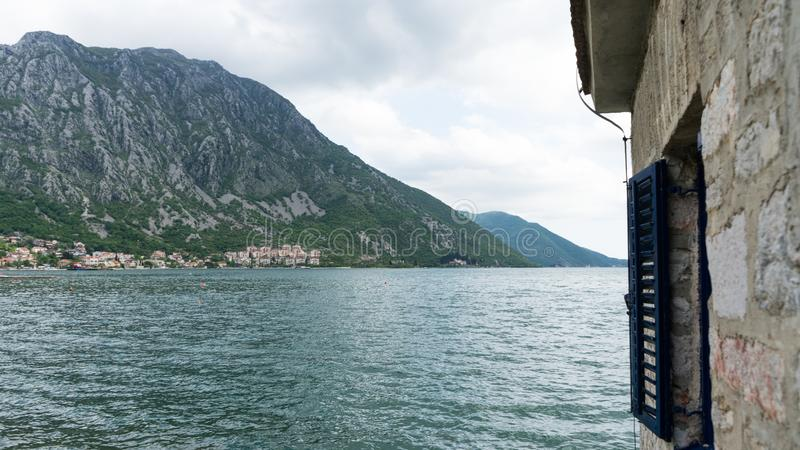 Coast town under the big mountains of Montenegro in Kotor bay. Old house abandoned in the sea. Cloudy day in small village and royalty free stock photo