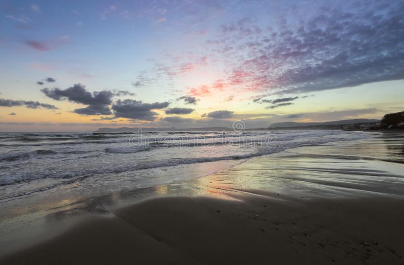 From the coast with wet sand, sea with waves, mountains there is a fantastic view of sunset sky. Nice warm summer day. From the coast with wet sand, sea with royalty free stock photography