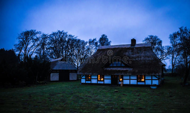 Coastal beach house with thatched roof. In the evening royalty free stock photos