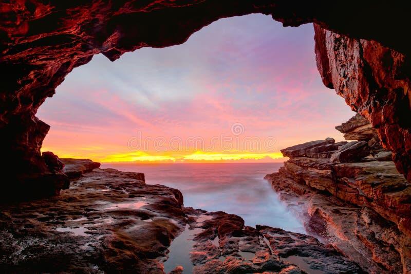 Coastal cave views to glorious sunrise over the ocean stock photos