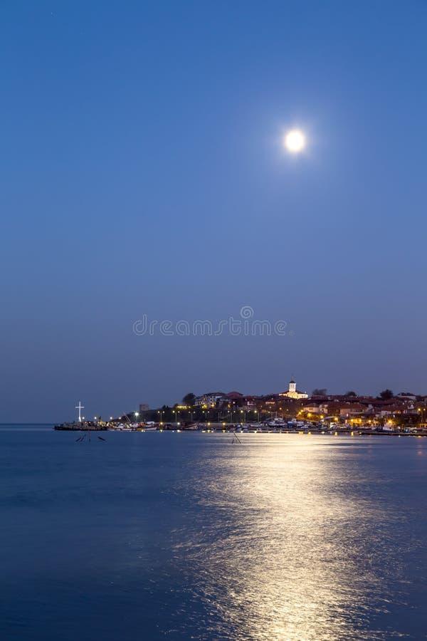 Coastal city at night. And full moon in sky stock photos