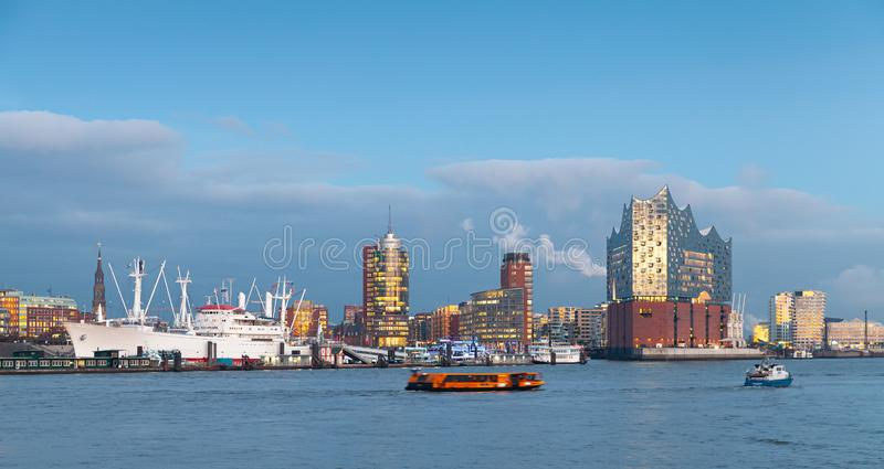 Coastal cityscape of Hamburg, Germany. Cityscape of Hamburg, Germany with modern and old buildings at evening stock photos