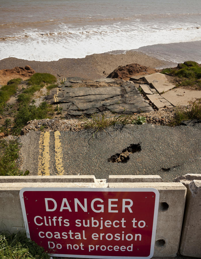Coastal erosion. Road and cliffs collapsing into sea, east coast of England, with warning sign in foreground royalty free stock photography