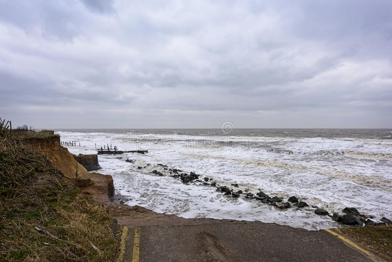 Coastal erosion taking place during a winter storm. UK, HAPPISBURGH - 18 MAR 2018: Coastal errosion taking place duirng a winter storm. Many homes have recently royalty free stock photography
