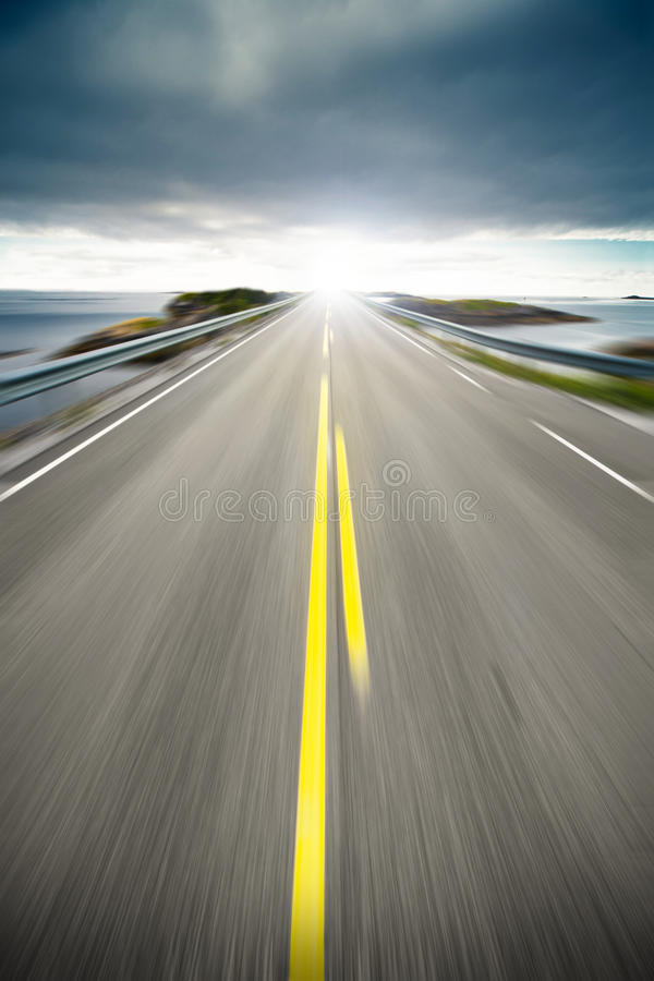 Coastal highway road in motion. Scenic view of coastal highway or road receding on coastline with slow motion blur and sunny background stock images