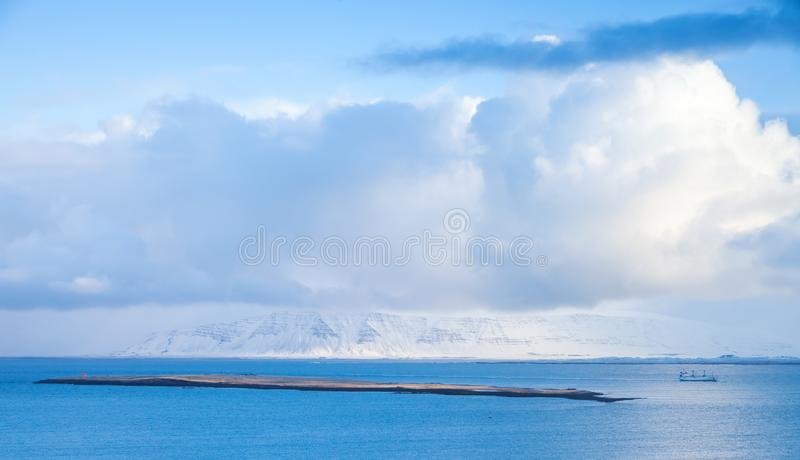Coastal Icelandic landscape with cargo ship. Going near small islet and snowy mountains under dramatic blue sky. Reykjavik area, Iceland stock photos