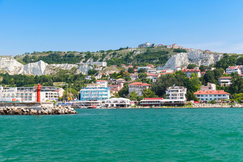 Coastal landscape of Balchik resort town. Entrance to port, red lighthouse on the pier. Coast of the Black Sea, Varna region, Bulgaria royalty free stock photo