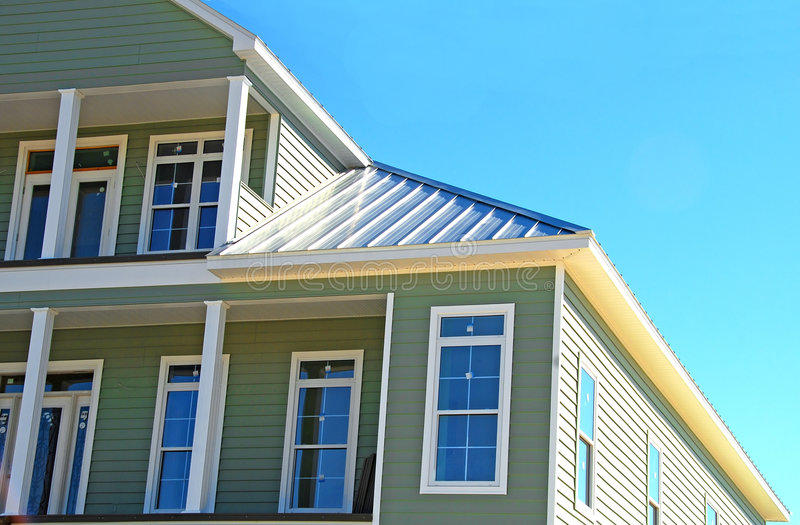 Coastal New Home. Beautiful newly build coastal home with tin roof under blue sky royalty free stock photos