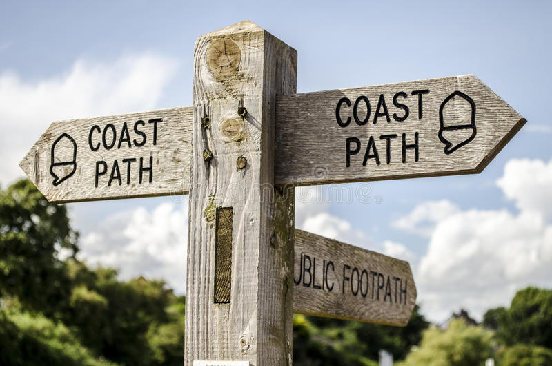 Coastal Path Sign. A close up of a coastal path sign in Devon. Blue sky in background with white clouds royalty free stock images