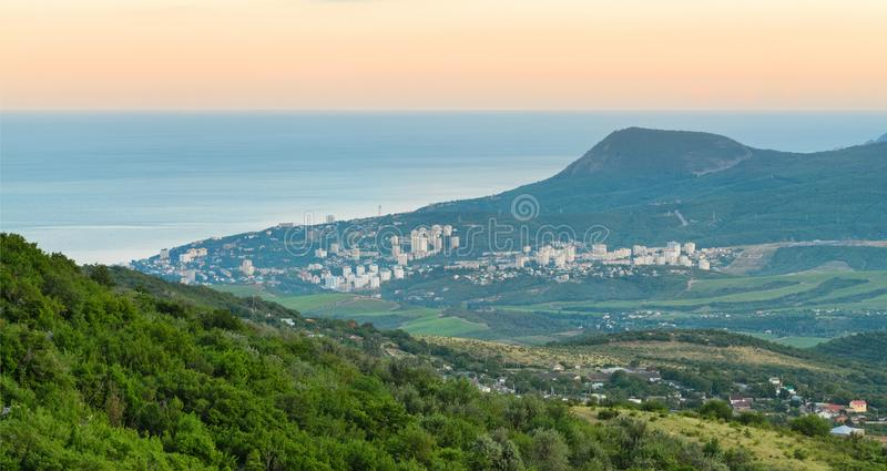 Coastal resort town between the mountains and hills near the sea at dawn. The Peninsula of Crimea, Alushta royalty free stock photography