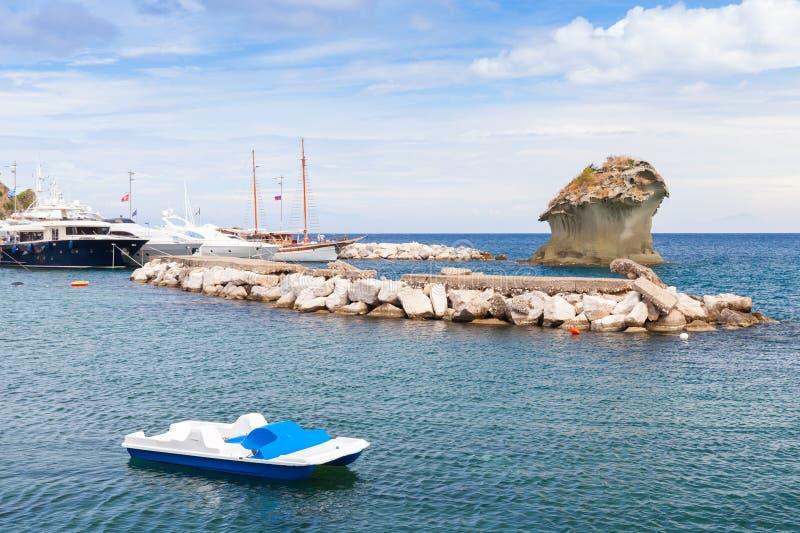 Coastal seascape of Lacco Ameno, Ischia island. Italy. Small white catamaran and Il Fungo, mushroom shaped rock on a background stock image