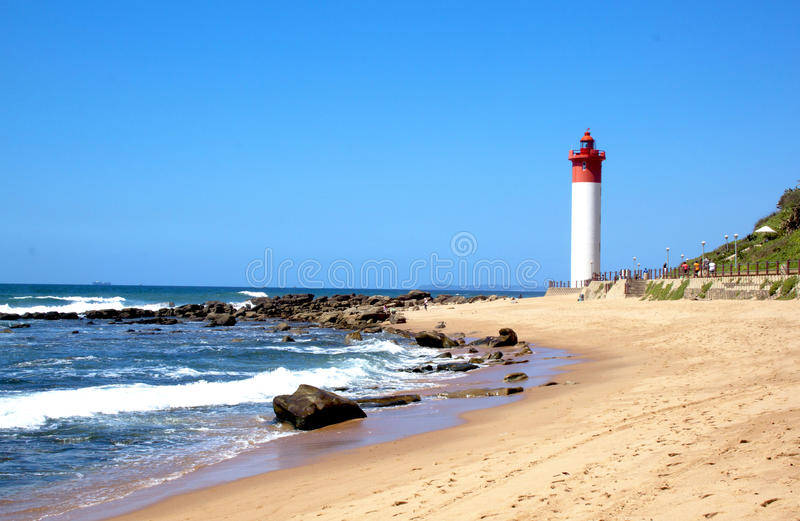 Coastal Seascape With Red and White lighthouse. Coastal seascape with beach ocean and lighthouse at Umhlanga Durban South Africa royalty free stock images
