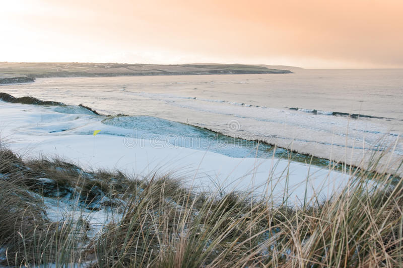 Coastal snow covered links golf course at sunset royalty free stock photo