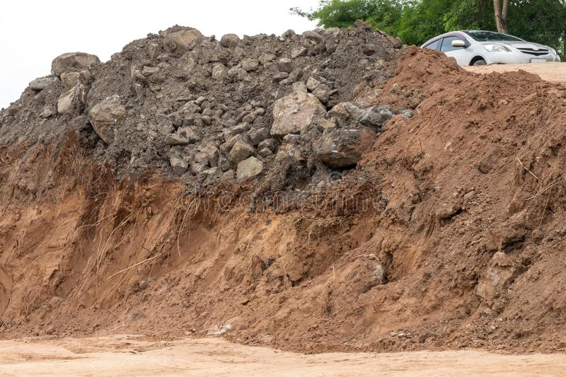 Coastal soil was dug under a pile of rocks. Close-up background of the eroded riverbank soil, which was excavated under the rocks and car above stock photo
