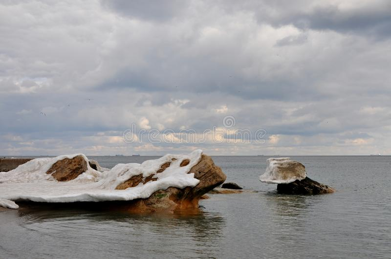 Coastal stones in the Black Sea peep out from under the growths of melting snow and ice. The end of winter. Cloudy sky, ships in the distance on a raid stock photos
