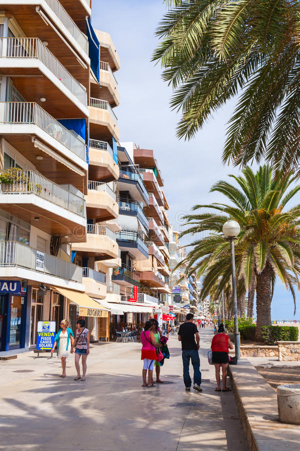 Coastal street of Calafell resort town in Spain. Calafell, Spain - August 20, 2014: Tourists walk on main coastal street of Calafell resort town in sunny summer stock photography